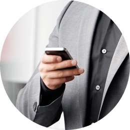 Roundel of a man wearing a gray suit and black shirt holding a smartphone