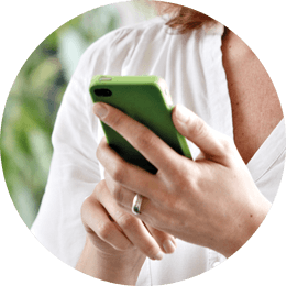 Roundel of a woman wearing a white top looking at a green smartphone