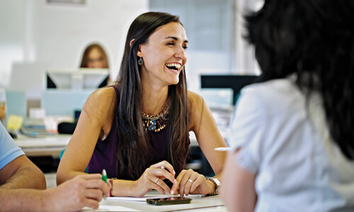 Woman with long dark hair wearing a black tank top sitting at a meeting table and laughing