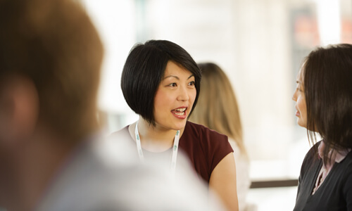 Woman with short dark hair talking to another woman in an office