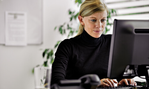 Businesswoman with blonde hair working at a computer