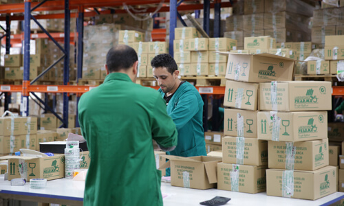 Two men in green overalls packing boxes in a warehouse