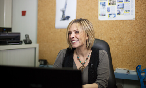 Smiling woman with blonde hair working on a computer in an office