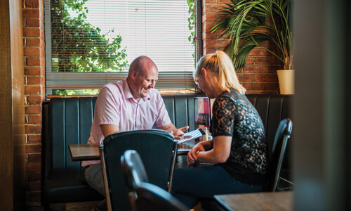 Man with a shaved head wearing a pink shirt sitting in a diner opposite a woman with blonde hair