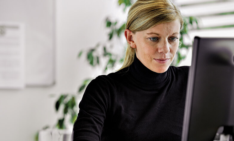 Businesswoman with blonde hair wearing a black turtleneck looking at a computer