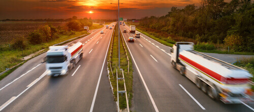 Trucks pass on opposite sides of a busy highway as the sun sets