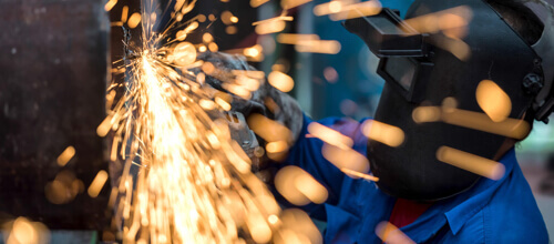 Sparks fly as a person with a welding mask welds metal